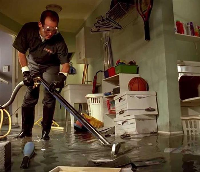 Male employee extracting water from a flooded room